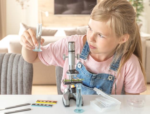 Menina aprendendo química brincando com o microscópio em casa Foto Premium
