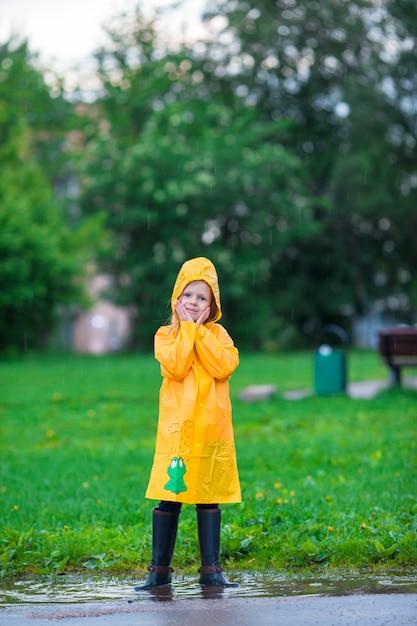 Menina aproveite a chuva em um dia quente de outono Foto Premium