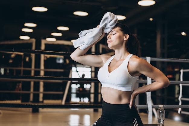 Menina apta de sorriso que guarda a toalha e o descanso no gym. menina limpa o suor com uma toalha Foto gratuita