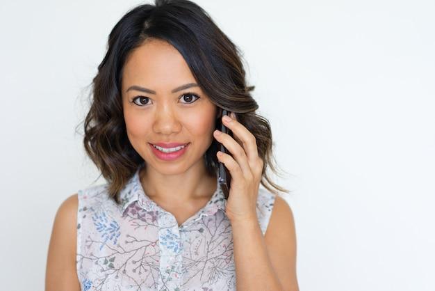 Menina asiática alegre falando no telefone Foto gratuita
