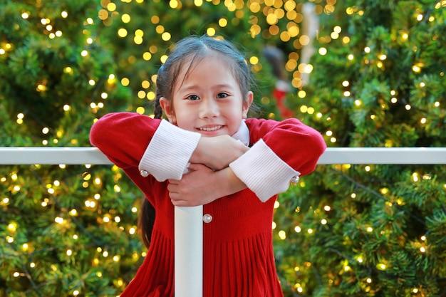 Menina asiática alegre no vestido vermelho se divertindo na temporada de inverno e festival de feliz ano novo contra o fundo de natal. Foto Premium