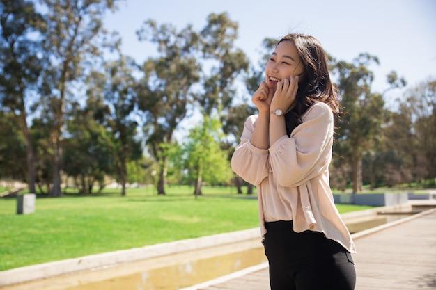Menina asiática animada falando no celular e rindo Foto gratuita