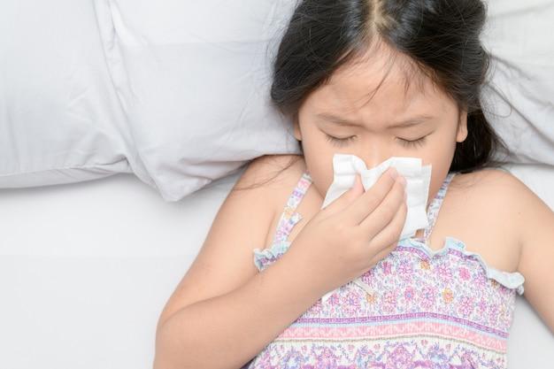 Menina asiática assoar o nariz por tecido Foto Premium
