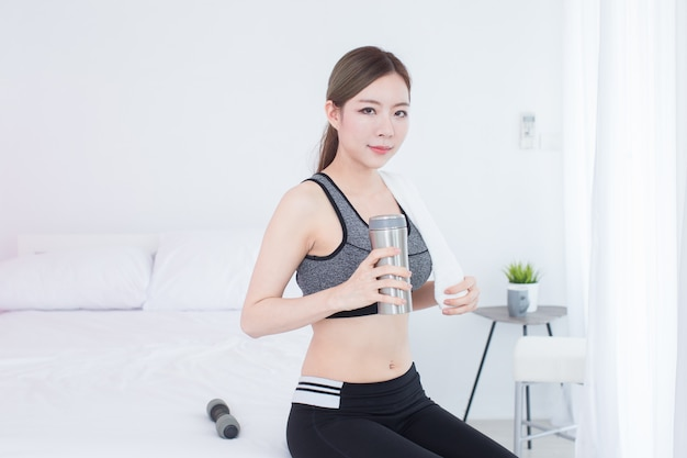 Menina asiática bonita jovem aptidão beber a garrafa de água após treino Foto Premium