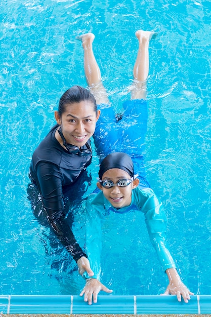 Menina asiática bonitinha aprendendo a nadar com o treinador no centro de lazer Foto Premium