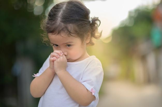 Menina asiática bonitinha fechou os olhos e rezando de manhã. mão asiática pequena da menina que reza, mãos dobradas no conceito da oração para a fé, a espiritualidade e a religião. Foto Premium