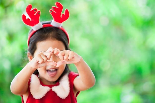 Menina asiática bonito da criança no vestido do natal que faz a forma do coração com mãos Foto Premium