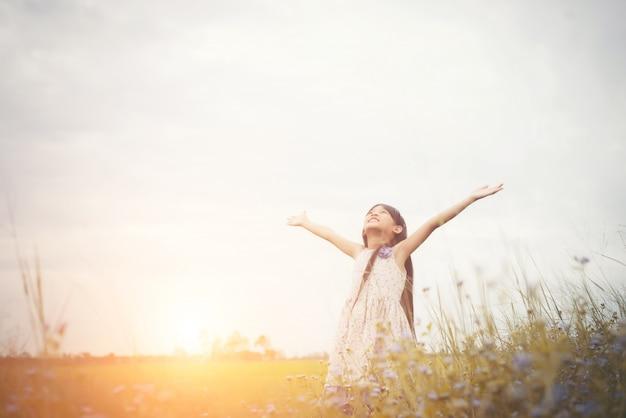Menina asiática bonito pequena que está entre o campo flor roxa su Foto gratuita
