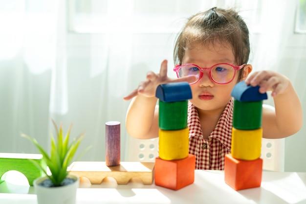Menina asiática brincando de bloco de madeira na sala de estar Foto Premium