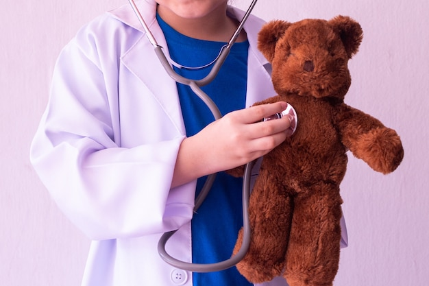 Menina asiática brincando de médico e ouvindo ursinho com estetoscópio Foto Premium
