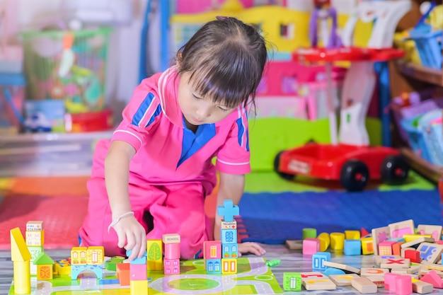 Menina asiática brincando no espaço brinquedos para crianças se desenvolvem na pré-escola, também conhecida como creche Foto Premium