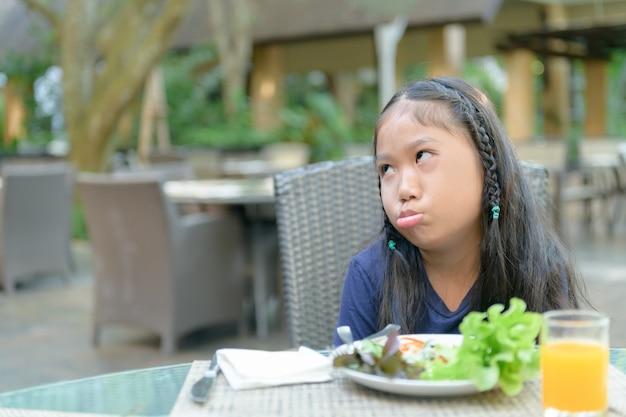 Menina asiática, com, expressão, de, nojo, contra, legumes Foto Premium