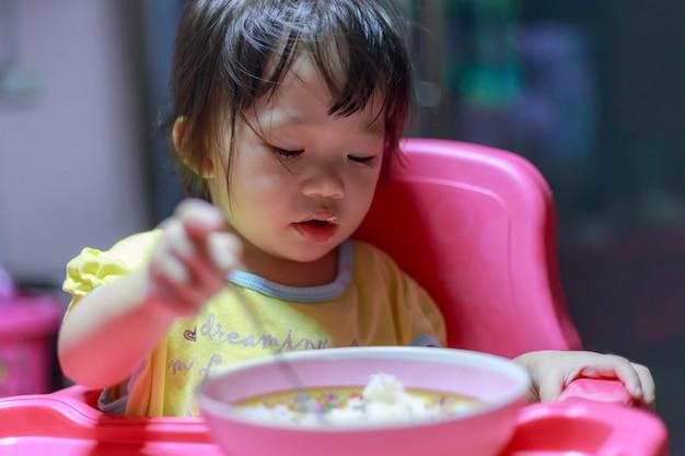Menina asiática comendo salsichas fritas na tigela de alumínio perto da janela em casa Foto Premium