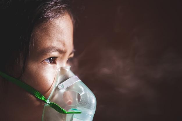 Menina asiática criança precisa de nebulização por obter máscara de inalador no rosto Foto Premium