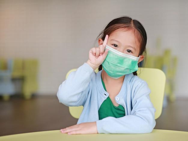 Menina asiática criança usando uma máscara protetora com mostrando um dedo indicador Foto Premium