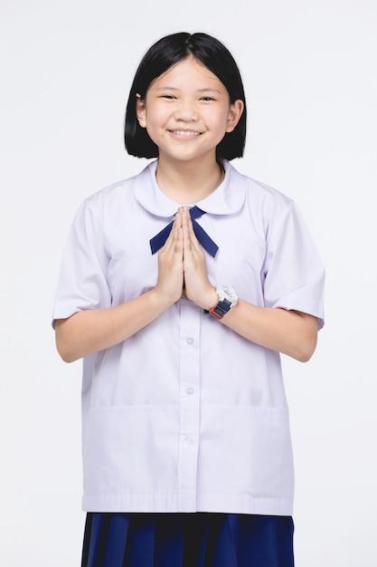 Menina asiática da criança no uniforme do estudante, meio do sawaddee da atuação olá! Foto Premium
