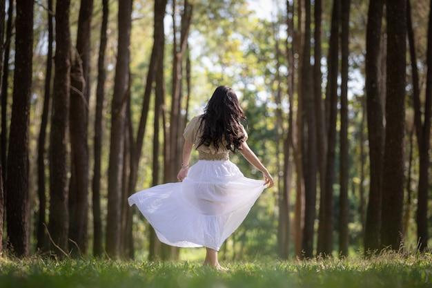Menina asiática das mulheres que anda no conceito da viagem das férias de verão da floresta do pinho Foto Premium