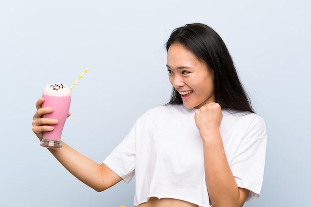 Menina asiática de adolescente segurando um milk-shake de morango comemorando uma vitória Foto Premium