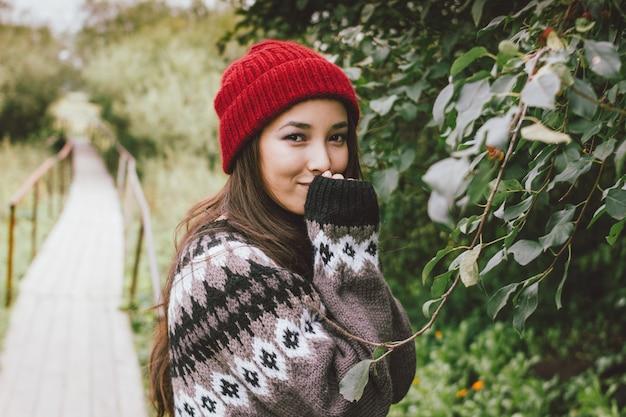 Menina asiática de cabelo comprido despreocupado bonito de chapéu vermelho e camisola nórdica de malha no parque natural de outono, estilo de vida de aventura de viagem Foto Premium