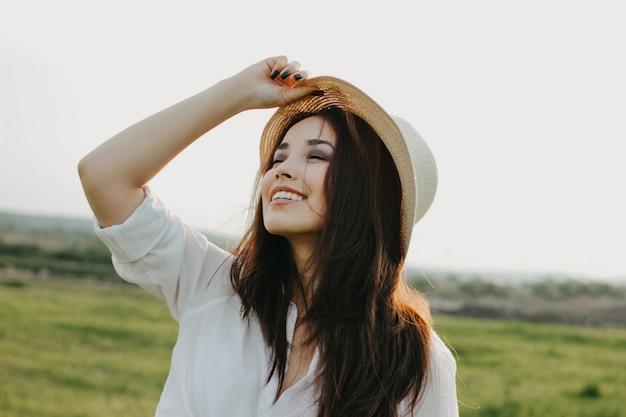 Menina asiática de cabelo comprido despreocupado bonito em roupas brancas e chapéu de palha aproveita a vida no campo da natureza ao pôr do sol Foto Premium