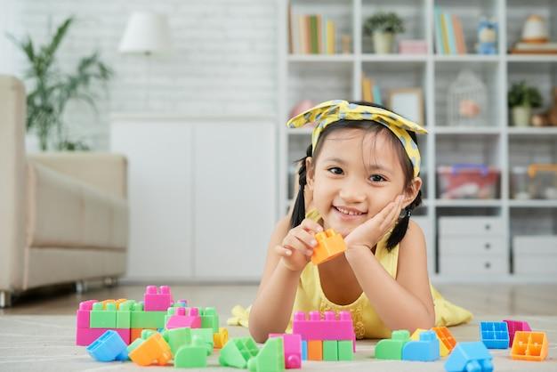 Menina asiática deitado no chão em casa e brincar com blocos de construção coloridos Foto gratuita