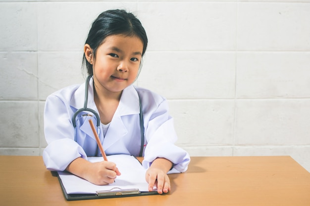 Menina asiática, desgastar, como, um, doutor, escrita, prescrição, e, preparar, pacientes, relatório Foto Premium