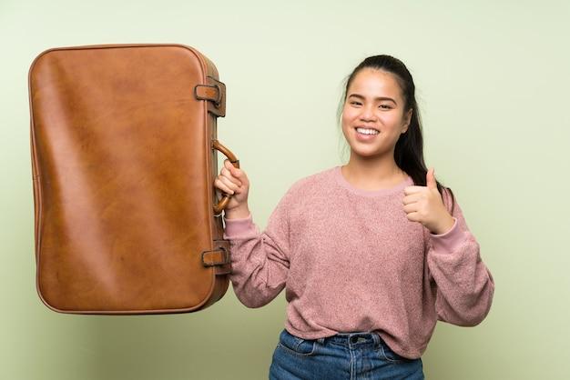 Menina asiática do jovem adolescente sobre fundo verde isolado, segurando uma maleta vintage Foto Premium