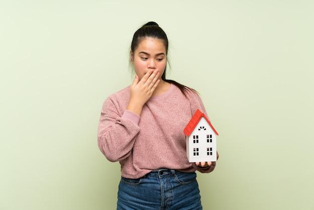 Menina asiática do jovem adolescente sobre parede verde isolada, segurando uma casinha Foto Premium