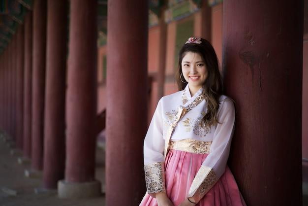Menina asiática do sorriso bonito novo que veste-se no retrato tradicional do estilo de hanbok Foto Premium