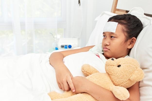 Menina asiática dormindo no hospital Foto Premium