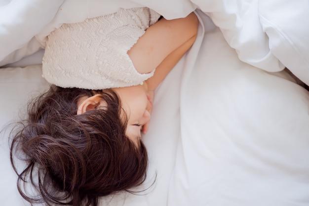 Menina asiática dormir na cama, criança doente, sono de criança Foto Premium