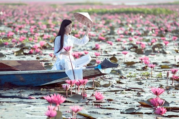 Menina asiática em traje nacional do vietnã, sentado no barco no mar vermelho de lótus em undon thani, tailândia. Foto Premium
