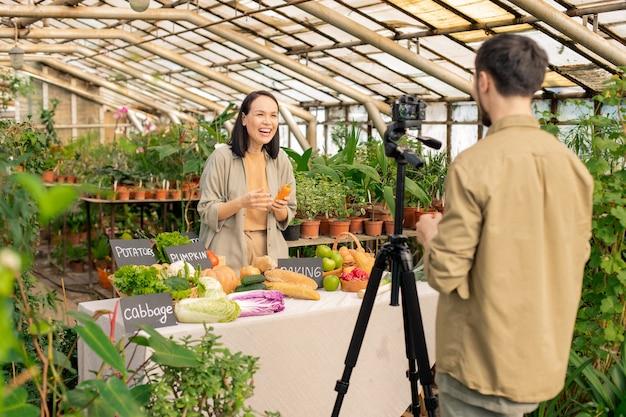 Menina asiática empolgada segurando uma cenoura e rindo enquanto faz um vídeo com um colega na estufa Foto Premium