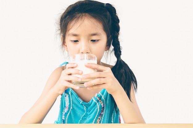 Menina asiática está bebendo um copo de leite sobre fundo branco Foto gratuita