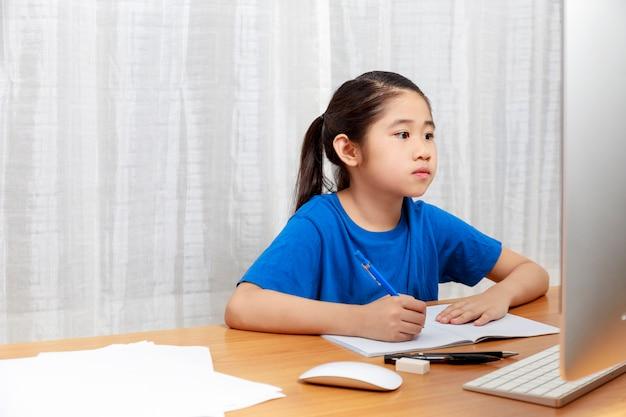 Menina asiática está estudando online através da internet, sentado e escrevendo na sala de estar em casa. crianças da ásia escrevendo com lápis no caderno. aprendizagem online em casa ou aprender com o conceito de casa. Foto Premium