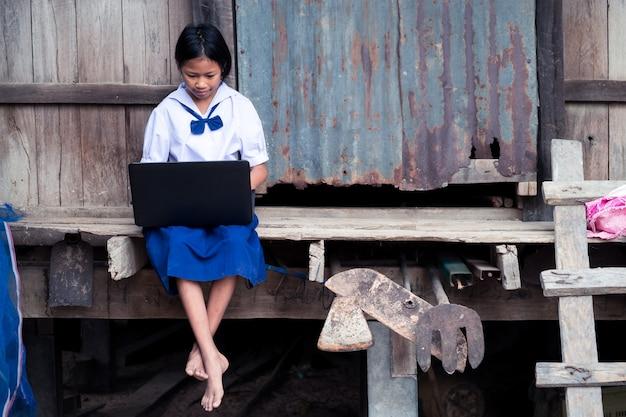 Menina asiática estudante uniforme usando computador notebook Foto Premium