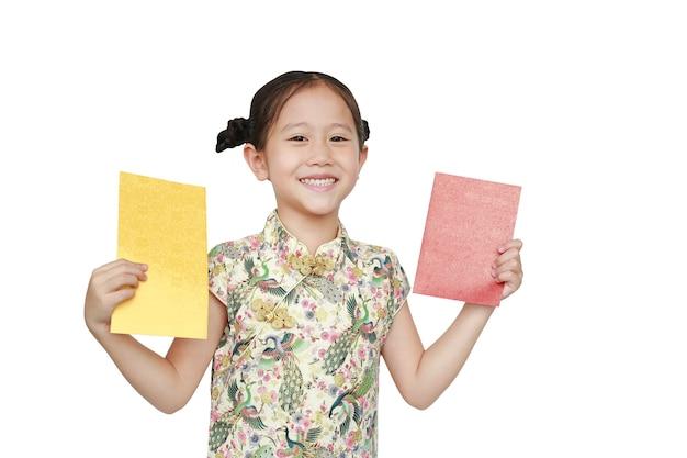 Menina asiática feliz vestindo cheongsam, sorrindo e segurando um envelope dourado e vermelho sobre fundo branco. Foto Premium