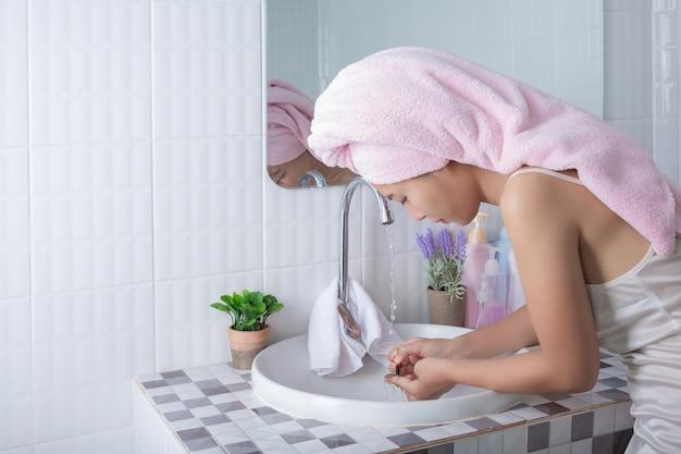 Menina asiática lava o rosto. Foto gratuita