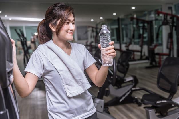 Menina asiática mão segure a garrafa de água potável na aptidão do clube de esporte e sorrindo Foto Premium