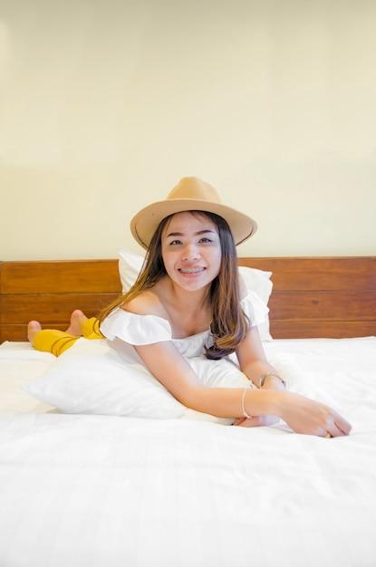 Menina asiática na cama branca Foto Premium