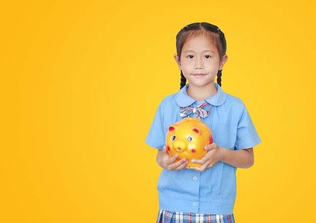 Menina asiática na farda da escola que mantém o mealheiro isolado com espaço da cópia. colegial com conceito de economia de dinheiro. Foto Premium