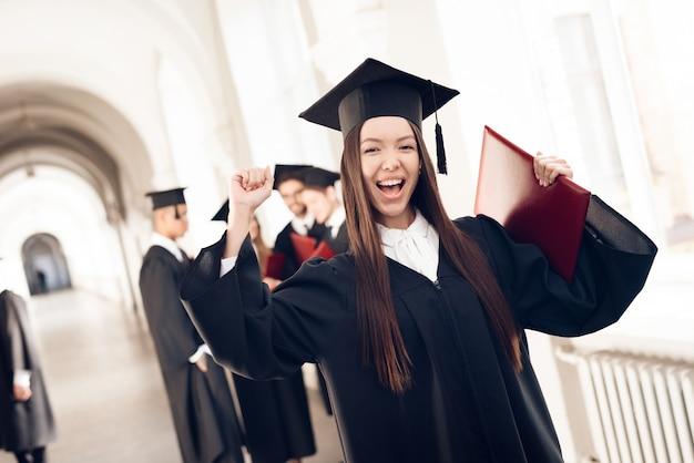 Menina asiática no manto está de pé no corredor da universidade Foto Premium