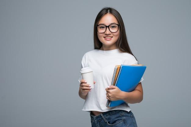 Menina asiática nova com caderno e café para ir nas mãos que estão isoladas contra o fundo cinzento Foto gratuita