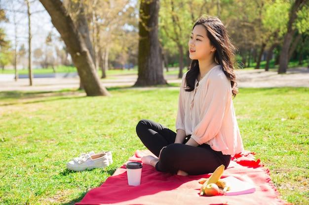 Menina asiática pacífica relaxante no parque Foto gratuita