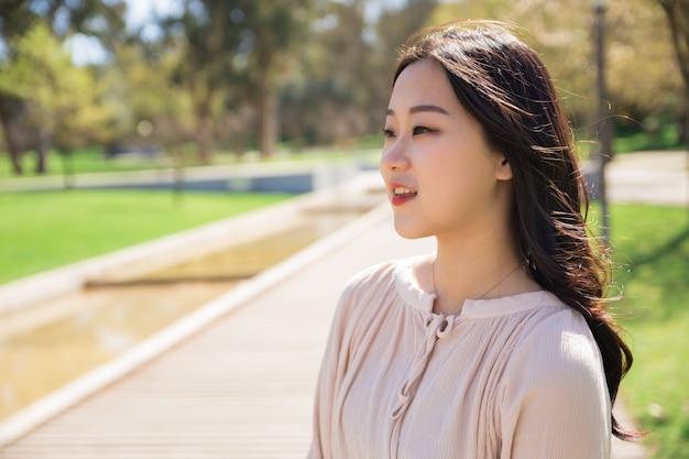Menina asiática pensativa, apreciando a paisagem no parque da cidade Foto gratuita