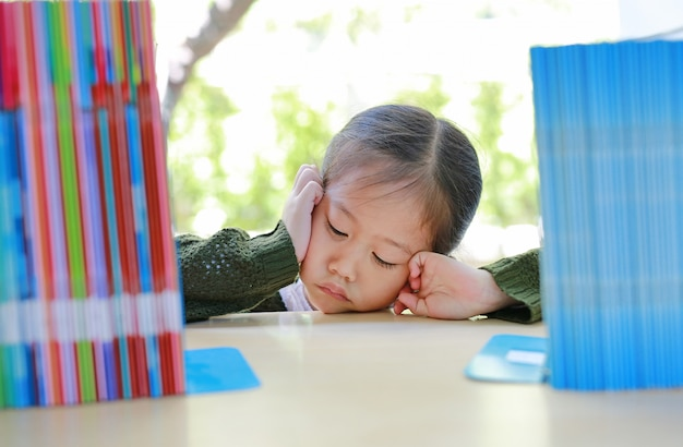Menina asiática pequena cansado que encontra-se na estante na biblioteca. Foto Premium
