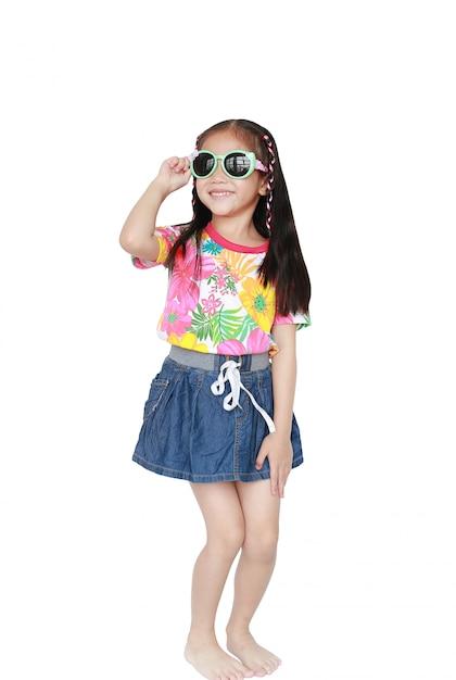Menina asiática pequena de sorriso da criança que veste um vestido do verão do teste padrão floral e óculos de sol isolados no fundo branco Foto Premium