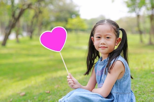 Menina asiática pequena feliz da criança que guarda a etiqueta vazia do coração que senta-se na grama verde no jardim exterior. Foto Premium