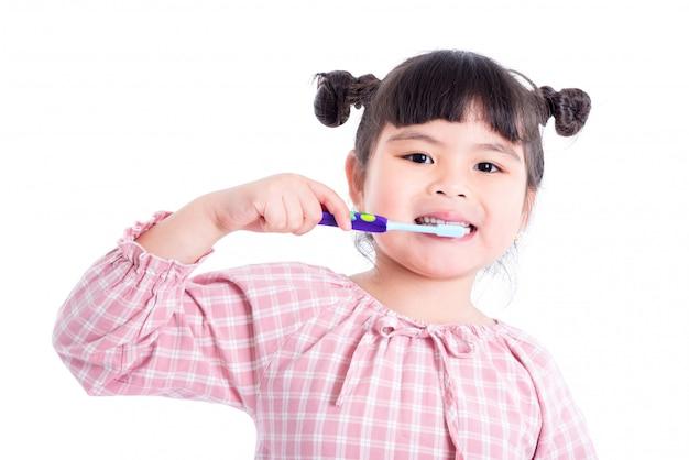 Menina asiática pequena segurando a escova de dentes e sorrisos sobre fundo branco Foto Premium