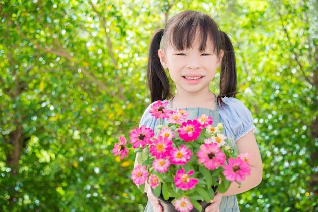 Menina asiática pequena segurando o vaso de flores e sorrisos no jardim Foto Premium
